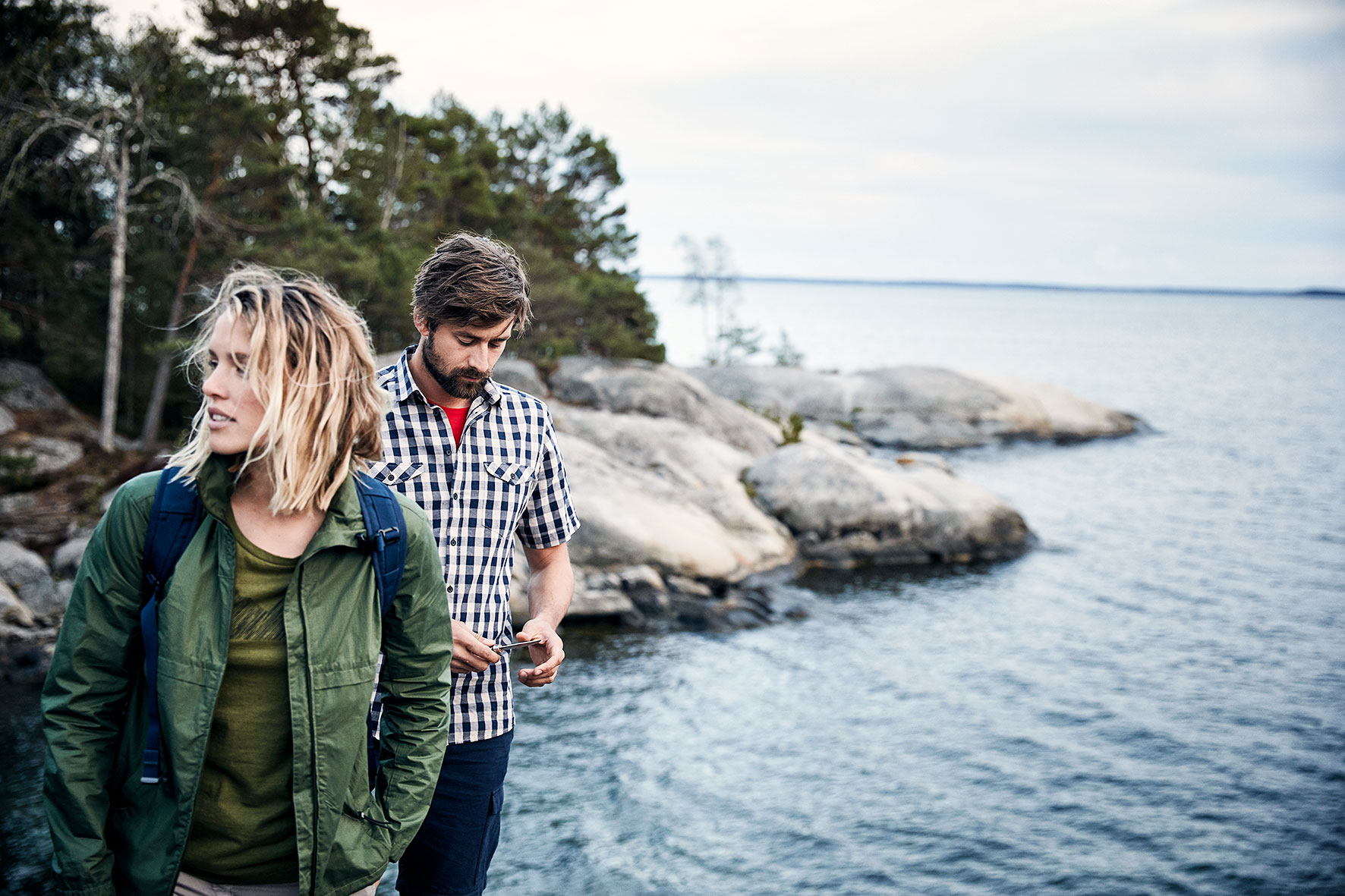 Couple standing on a cliff overlooking the sea near stockolm, Sweden. They are wearing outdoor clothing by a fair fashion brand Hess Natur