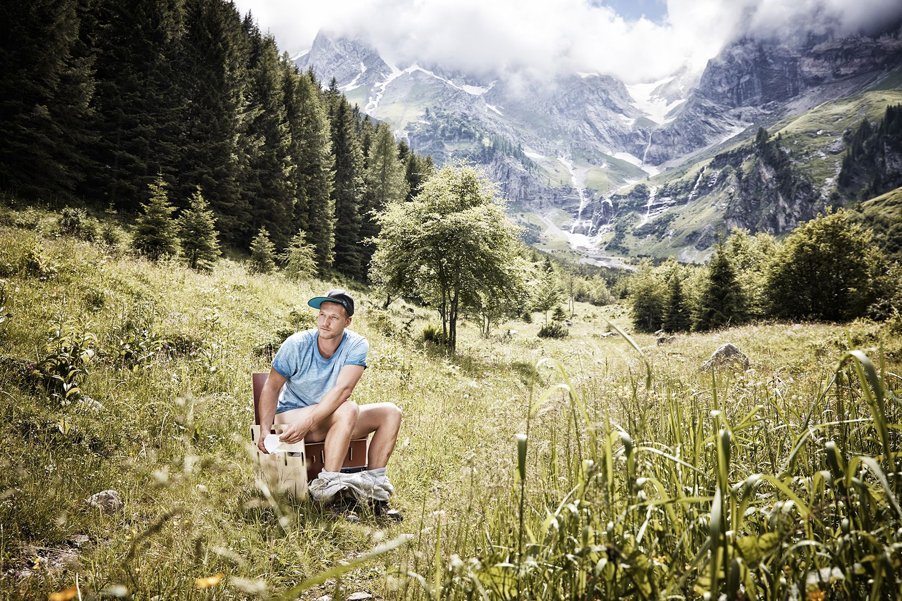 When nature calls - a man sitting on a portable toilet in the great outdoors