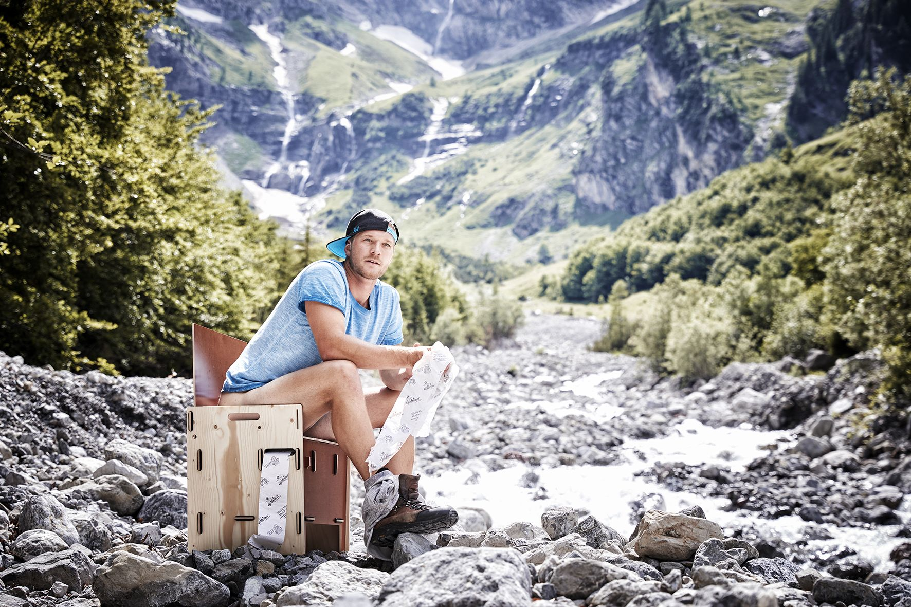 Toni sitting on a portable compost toilet in the middle of a river bed at the bottom of the mountain at Brandnertal, holding Goldeimer toilet paper in his hands.