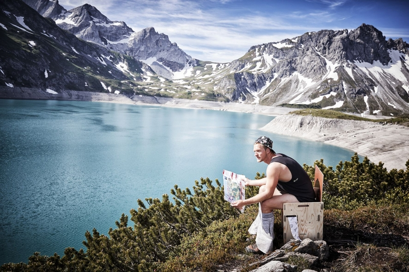 aerial photo of a man sitting on a toilet with a view of the luenersee and the mountains in the background