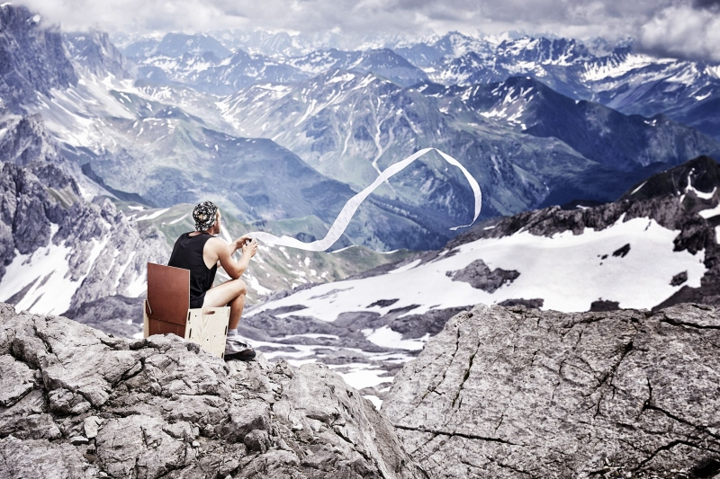 Landscape picture of a man sitting on on the top of the Schesaplana glacier with toilet paper flowing in the wind