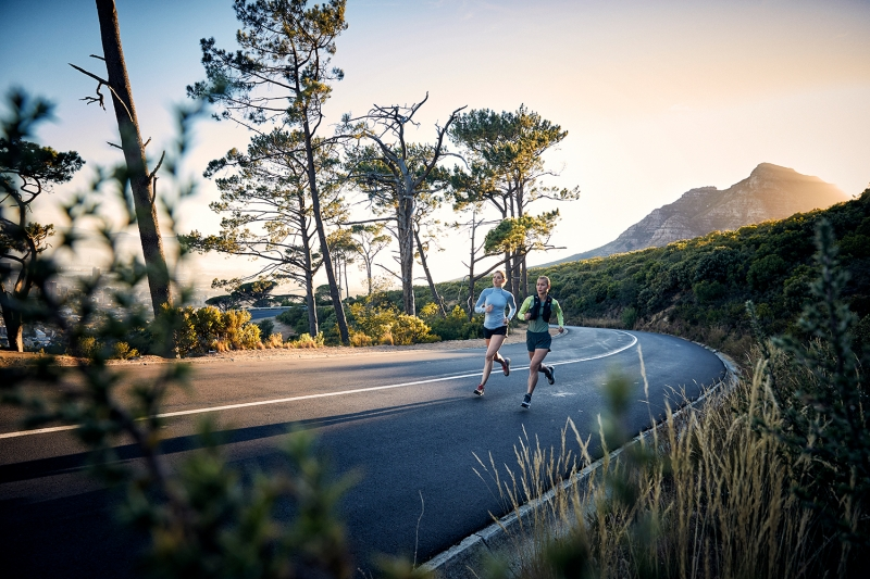 Two athletes training on the road by Table Mountain