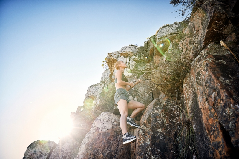 Athlete climbing up the chains on Table Mountain, Cape Town