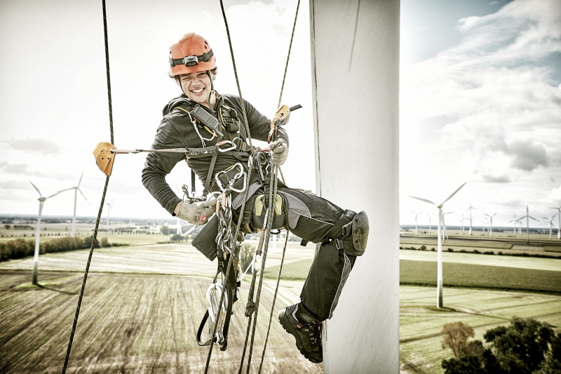 Wind Turbine Engineer grins into the camera while abseiling down a rotor blade