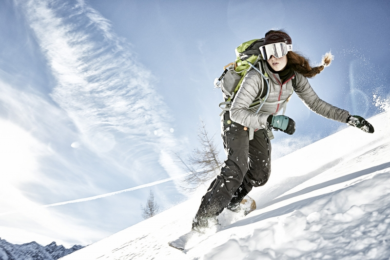 Woman snowboarder speeds down the mountain near Innsbruck