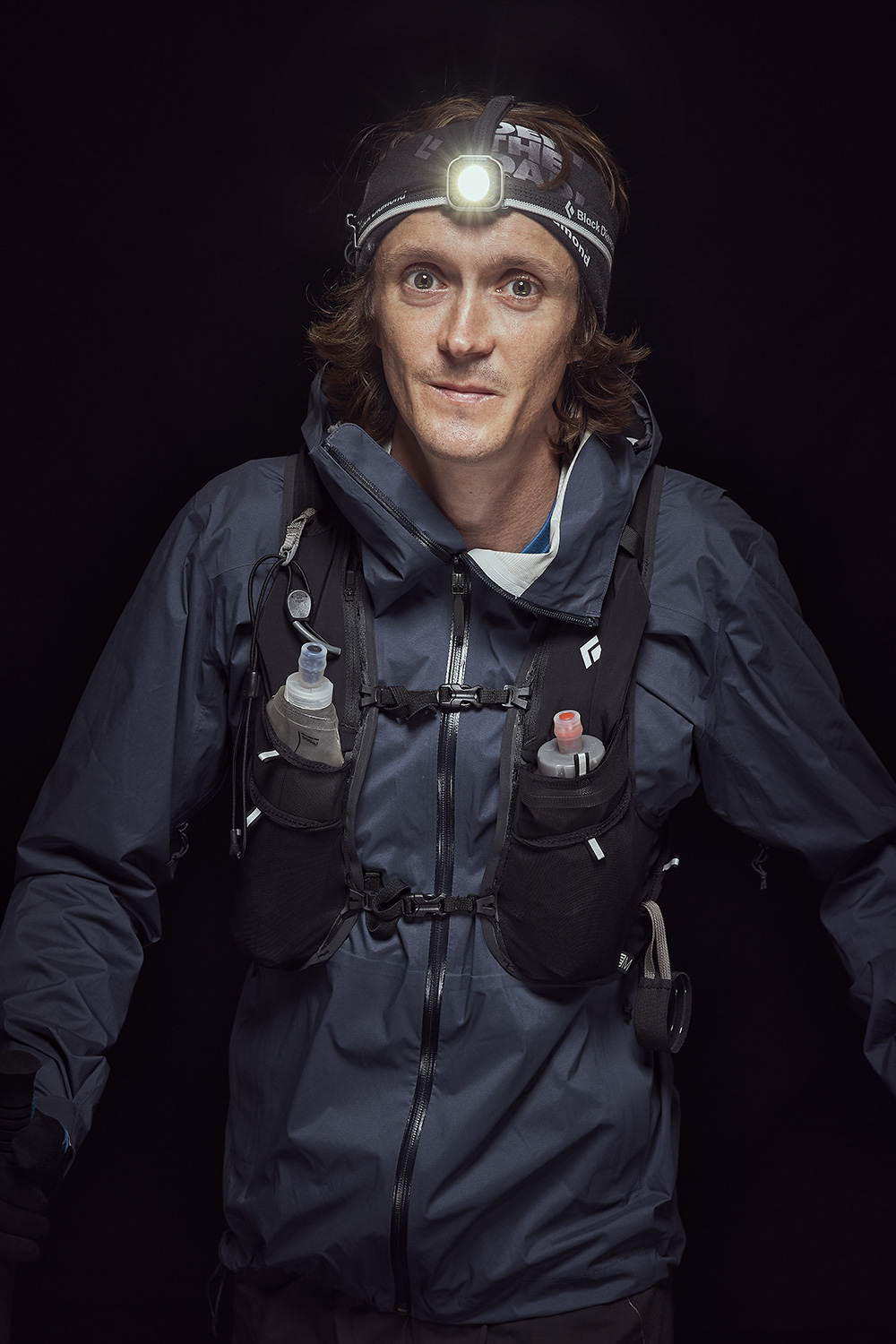 Portrait of trailrunner with his gear in studio
