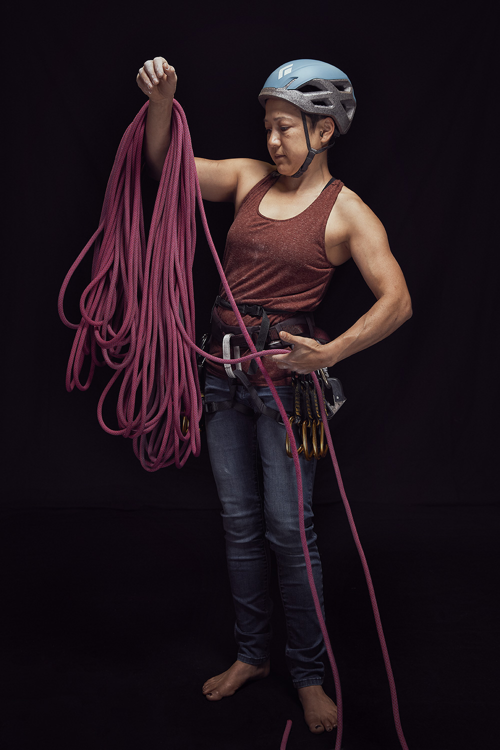 Porrtrait of woman mountain climber with her gear in studio