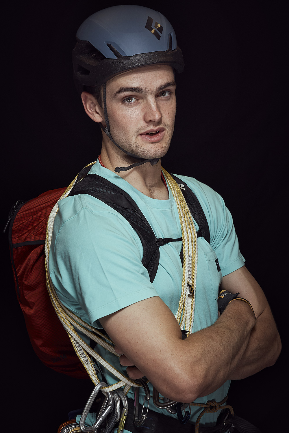 portrait of a mountain athlete with his gear infront of a black background
