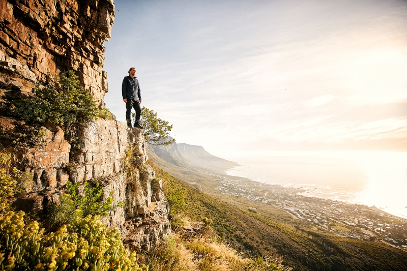 Young man overlooking Camps Bay from the top of Table Mountain