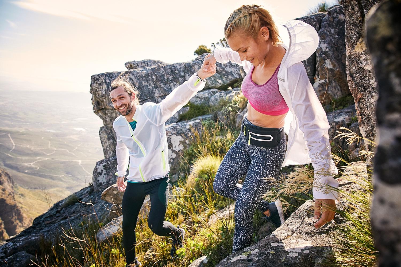 A Man and Woman scrambling over rocks at the du Tooitskloof mountain range.