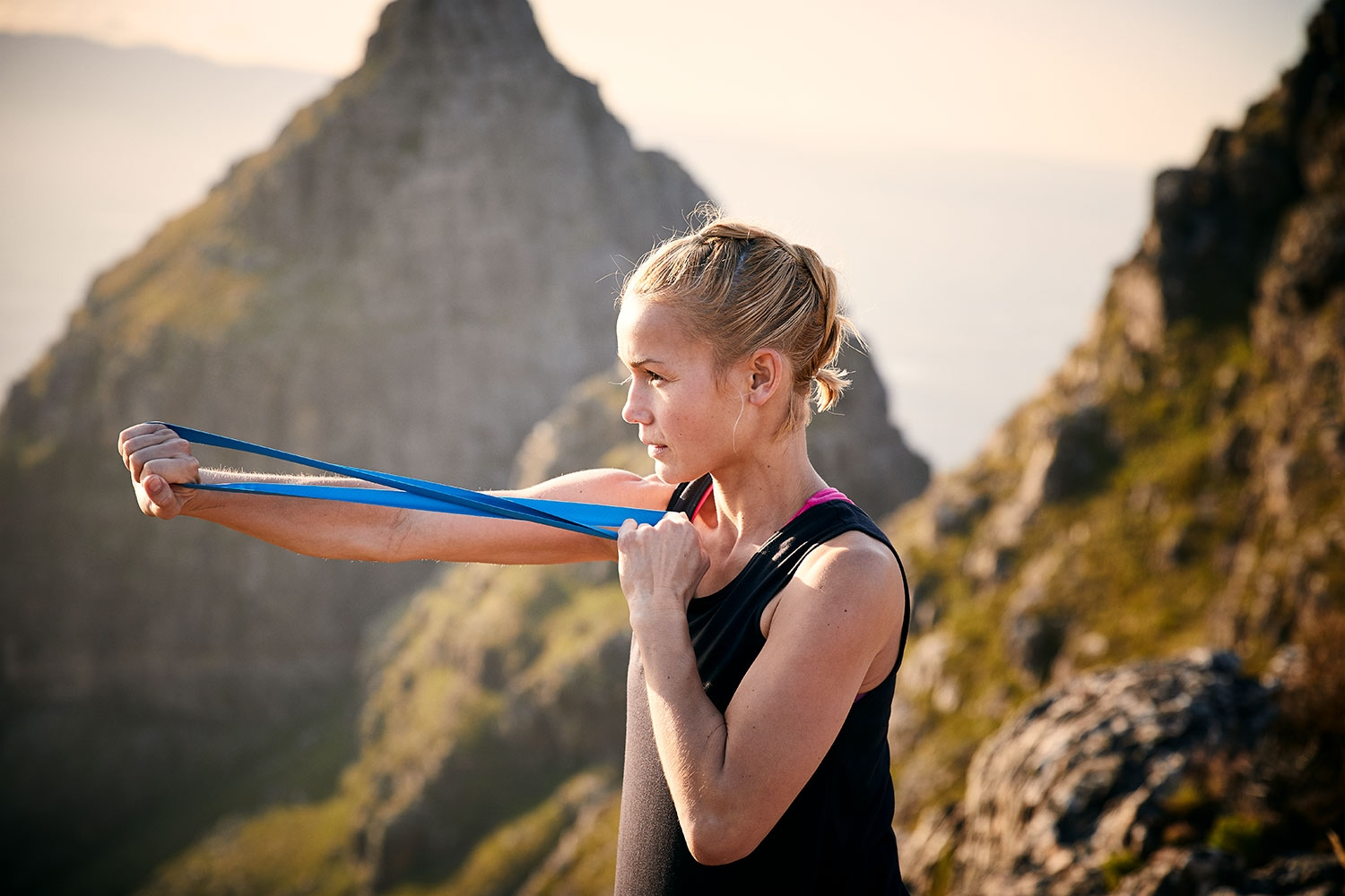 Young woman stretching with a terra band ontop of the du Tooitskloof mountains at sunset