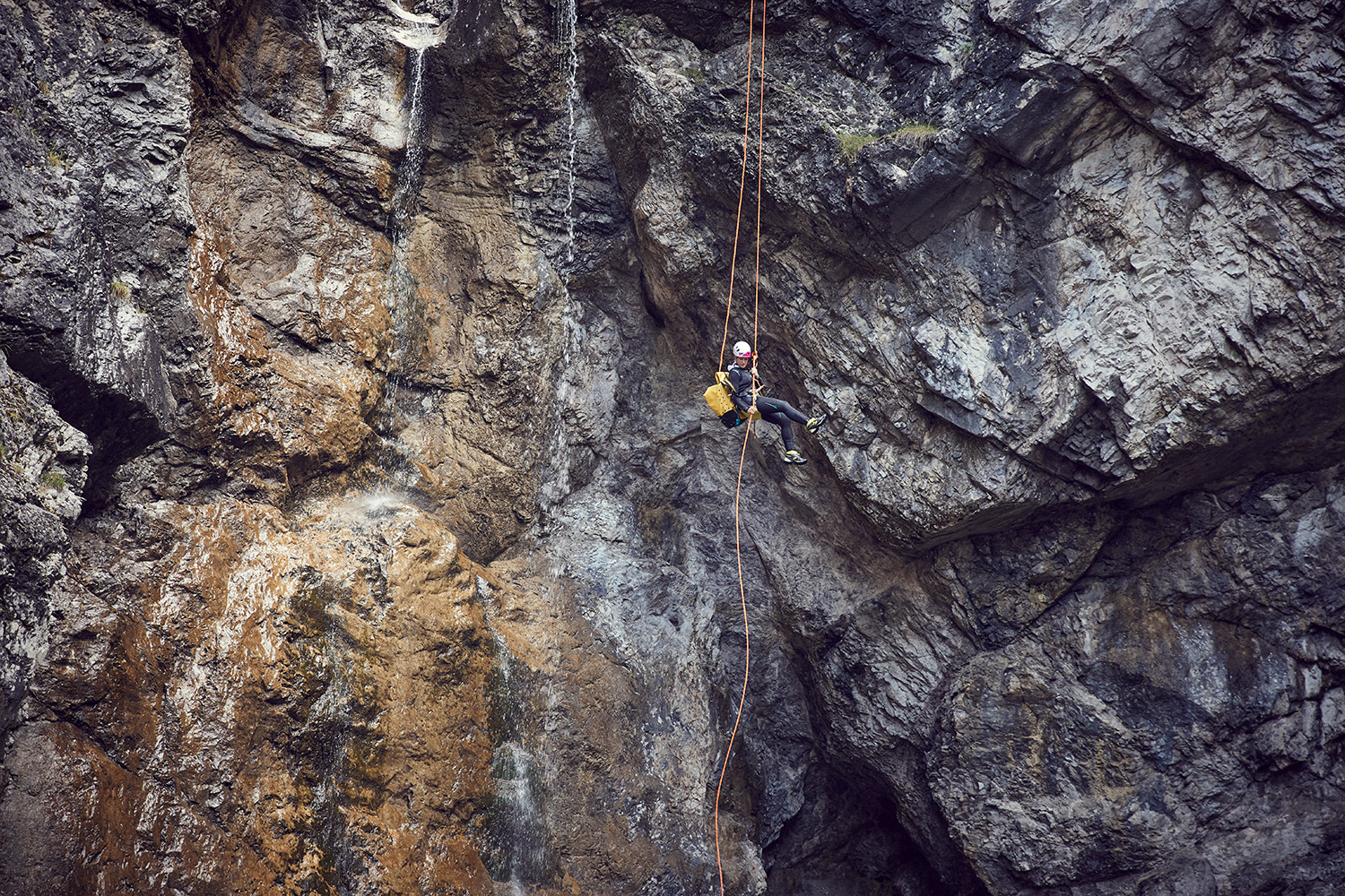 Stunt Woman Kim abseiling down a very high cliff on a canyoning tour in Austria