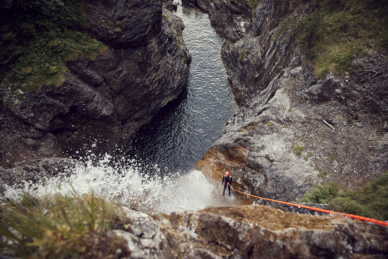 Malcolm abseiling through a waterfall into a black pool while canyoning in Austria