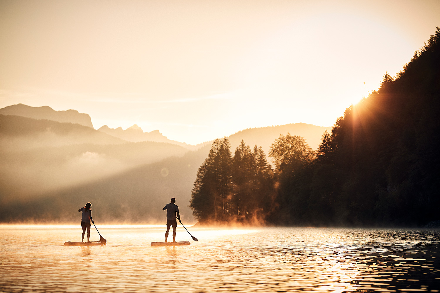 Golden hour at sunrise with a couple on stand up paddles at Walchensee Bavaria