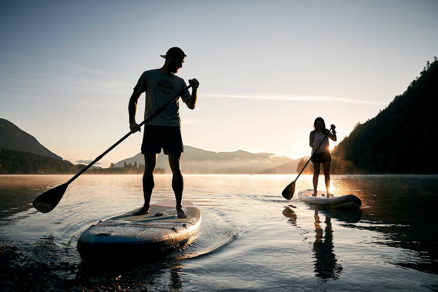 Silhouette of a couple on stand-up paddles in the sunrise at Walchensee