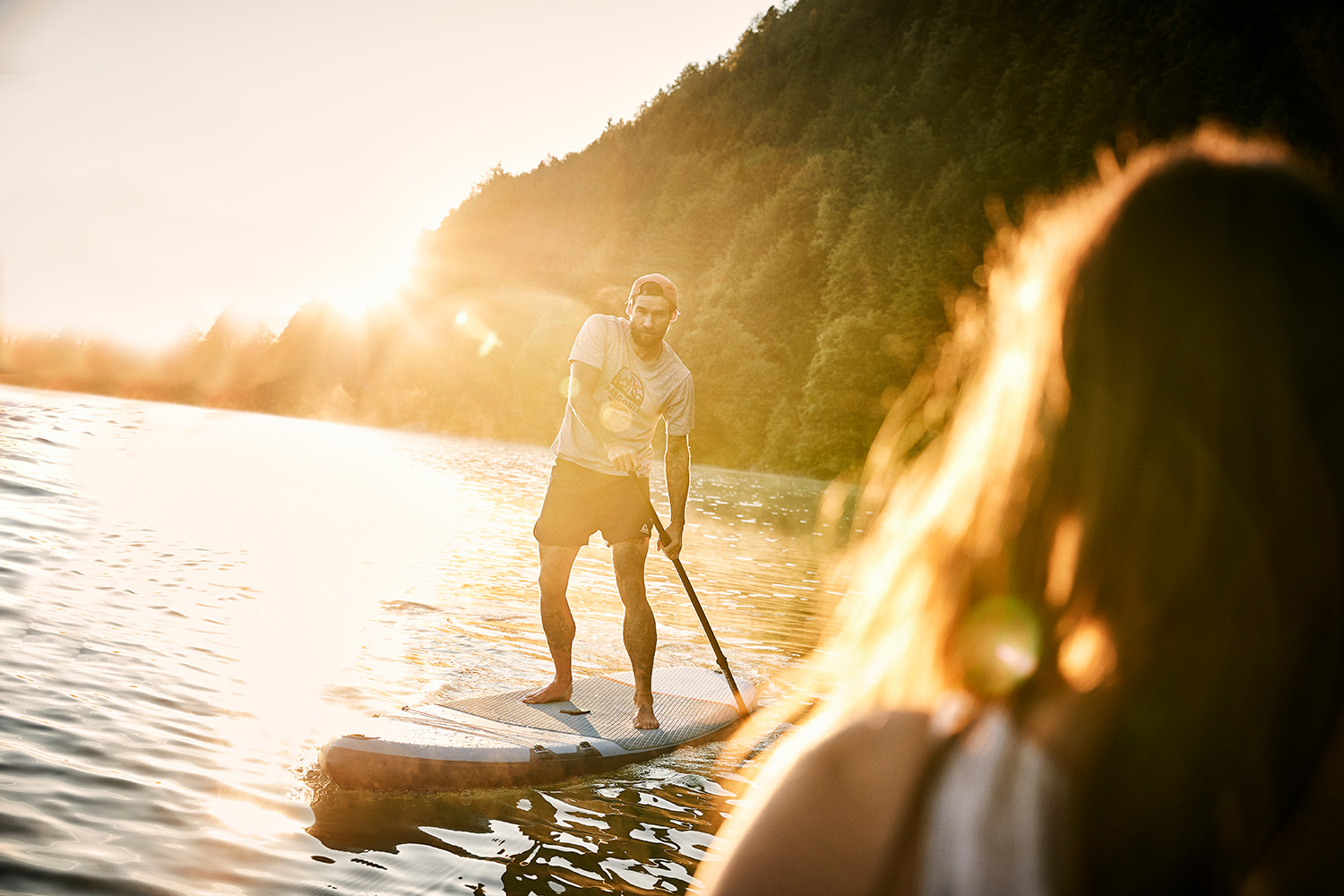 Man paddling towards a woman in the sunrise on a stand up paddle