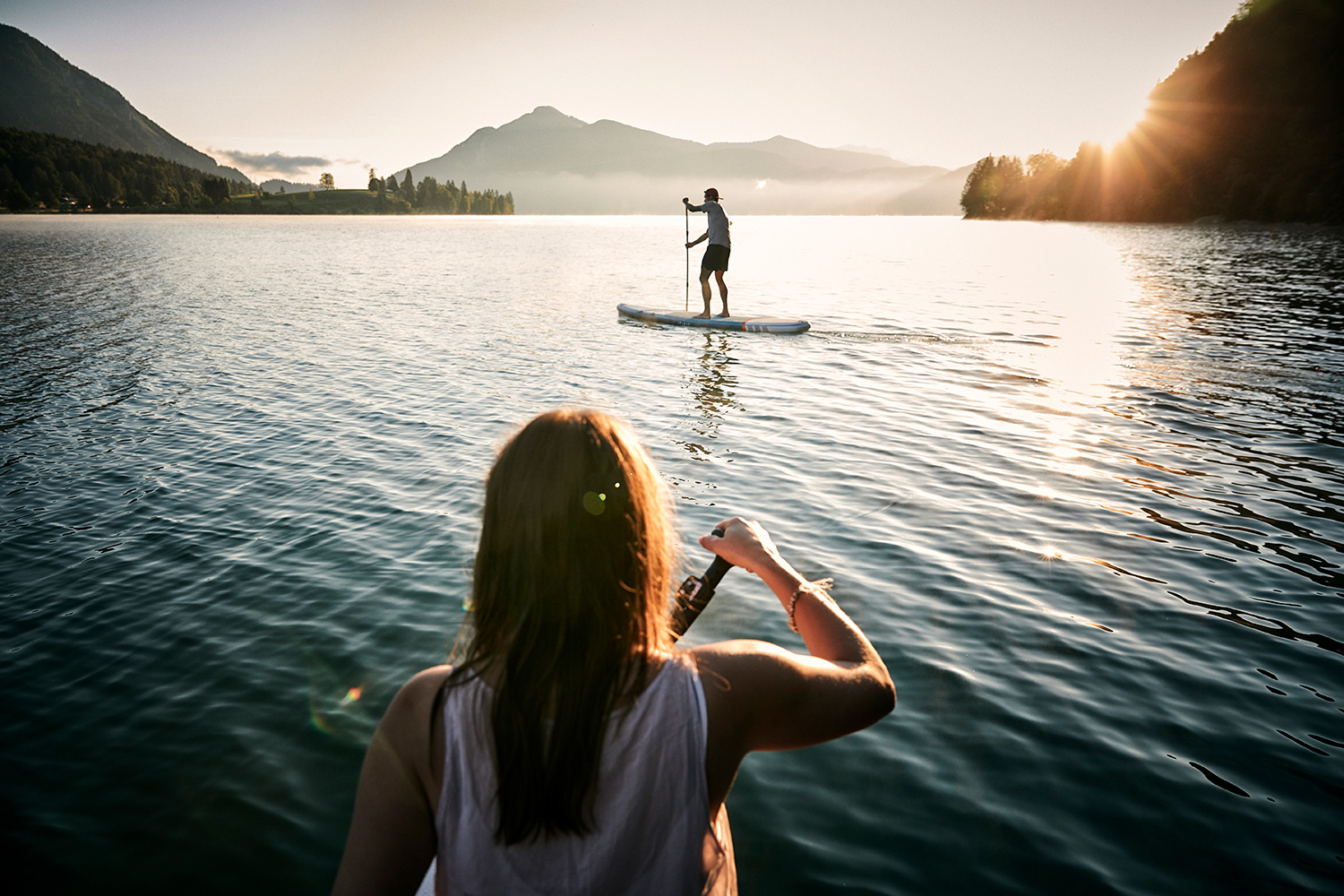 Couple on stand up paddles in the sunrise at Walchensee