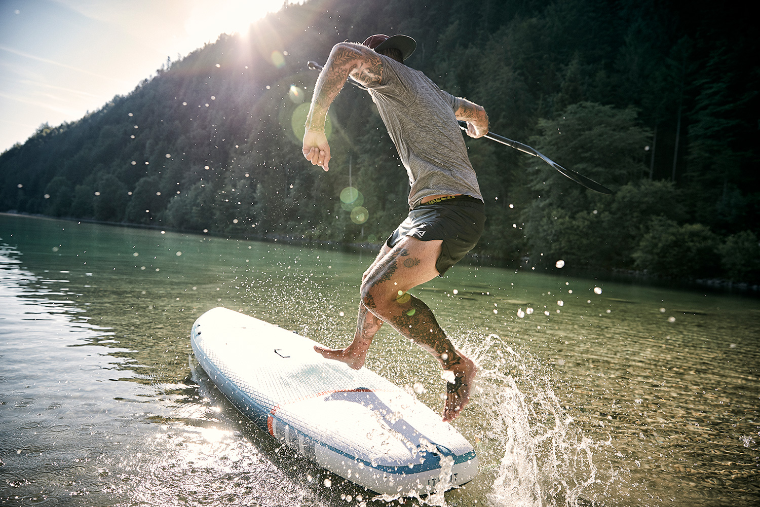 Danny jumping onto a sup at Walchensee with the water splashing around him