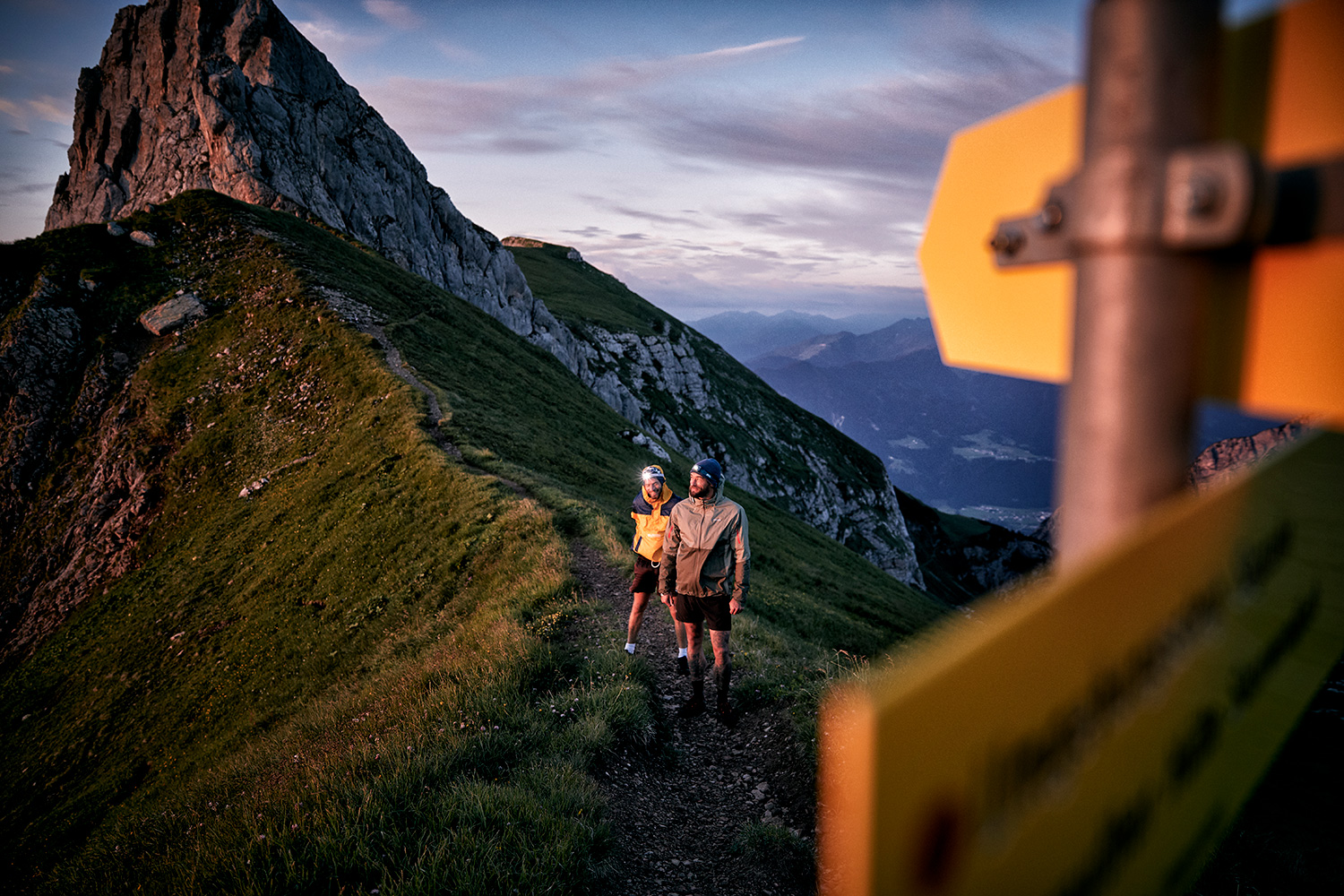 Two men trailrunning ontop of the Rofansspitze in the sunrise with a signpost in the foreground