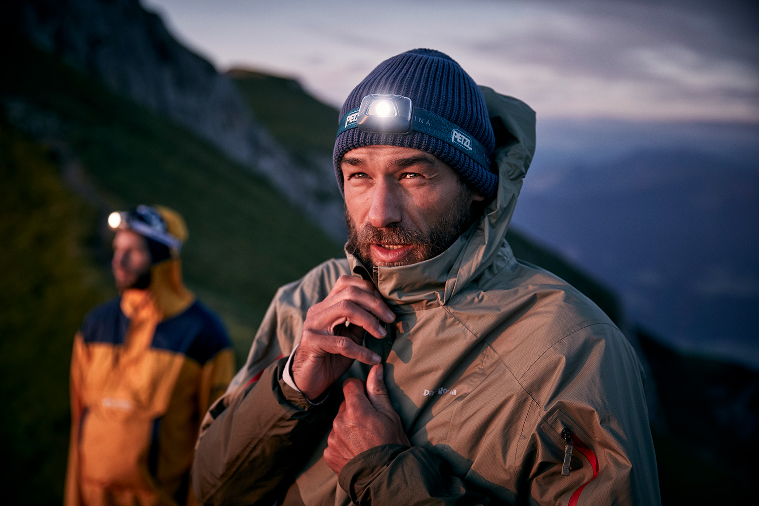 Portrait of a man closing his jacket while wearing a petzl headtorch while on a trailrun in the sunrises
