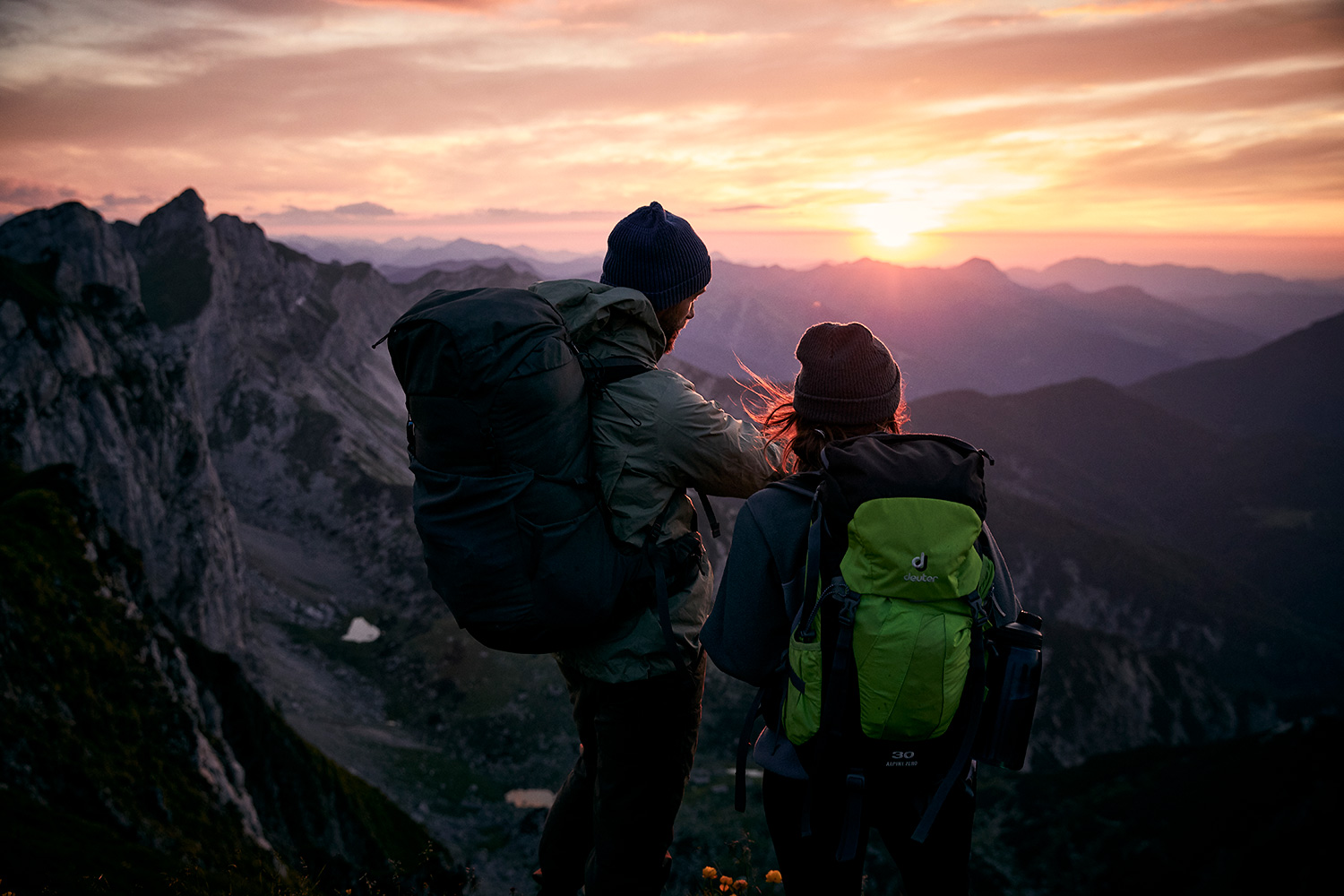 Couple watching the sunset ontop of the Rofanspitze in Austria