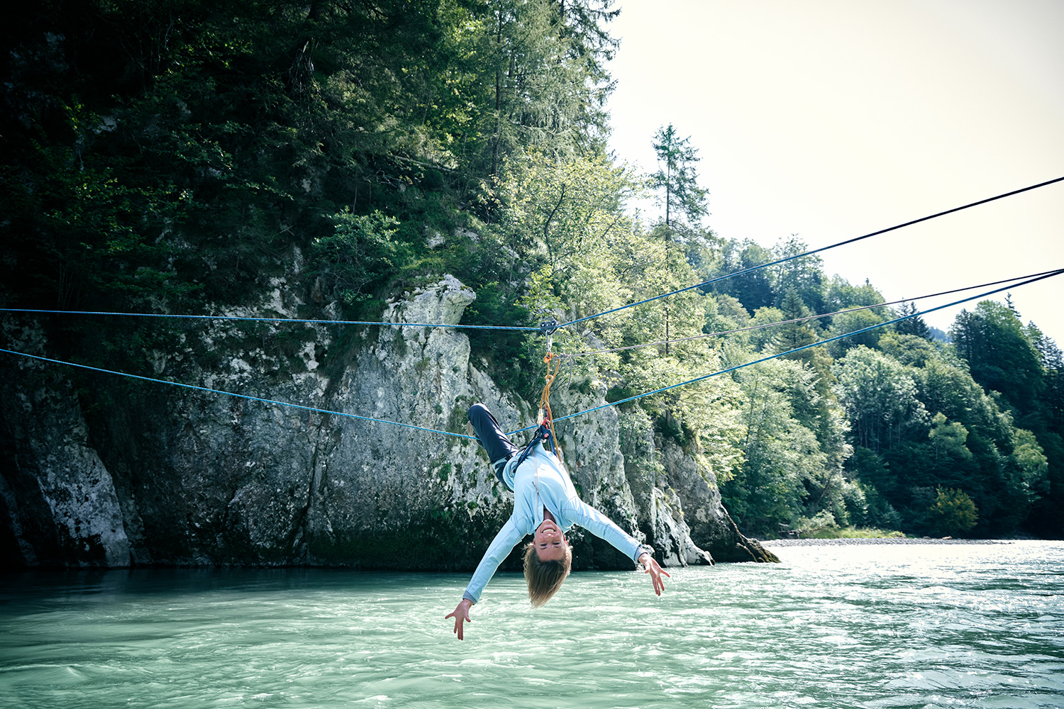 Woman hanging upside down on a rope over a river and making a peace sign