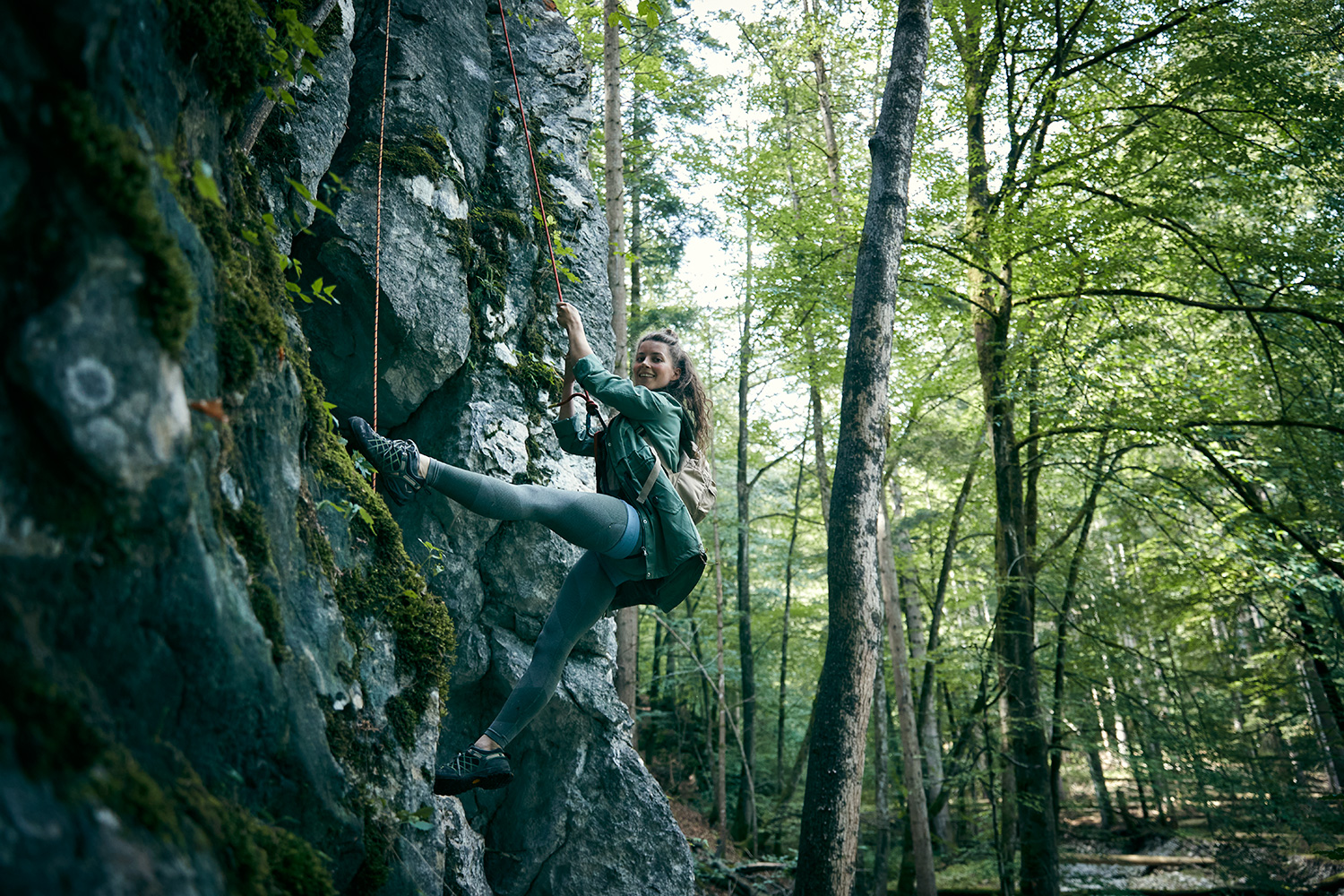 Woman doing the splits while abseiling down a rock