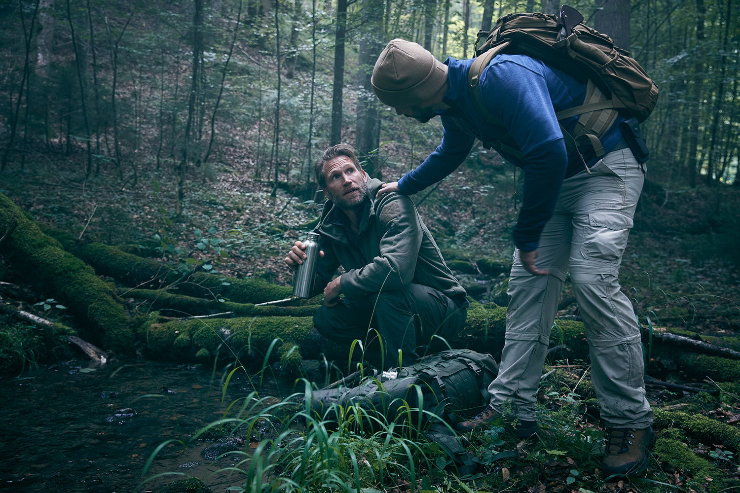 Survival trainer talking to a man drinking out of a stream in the woods