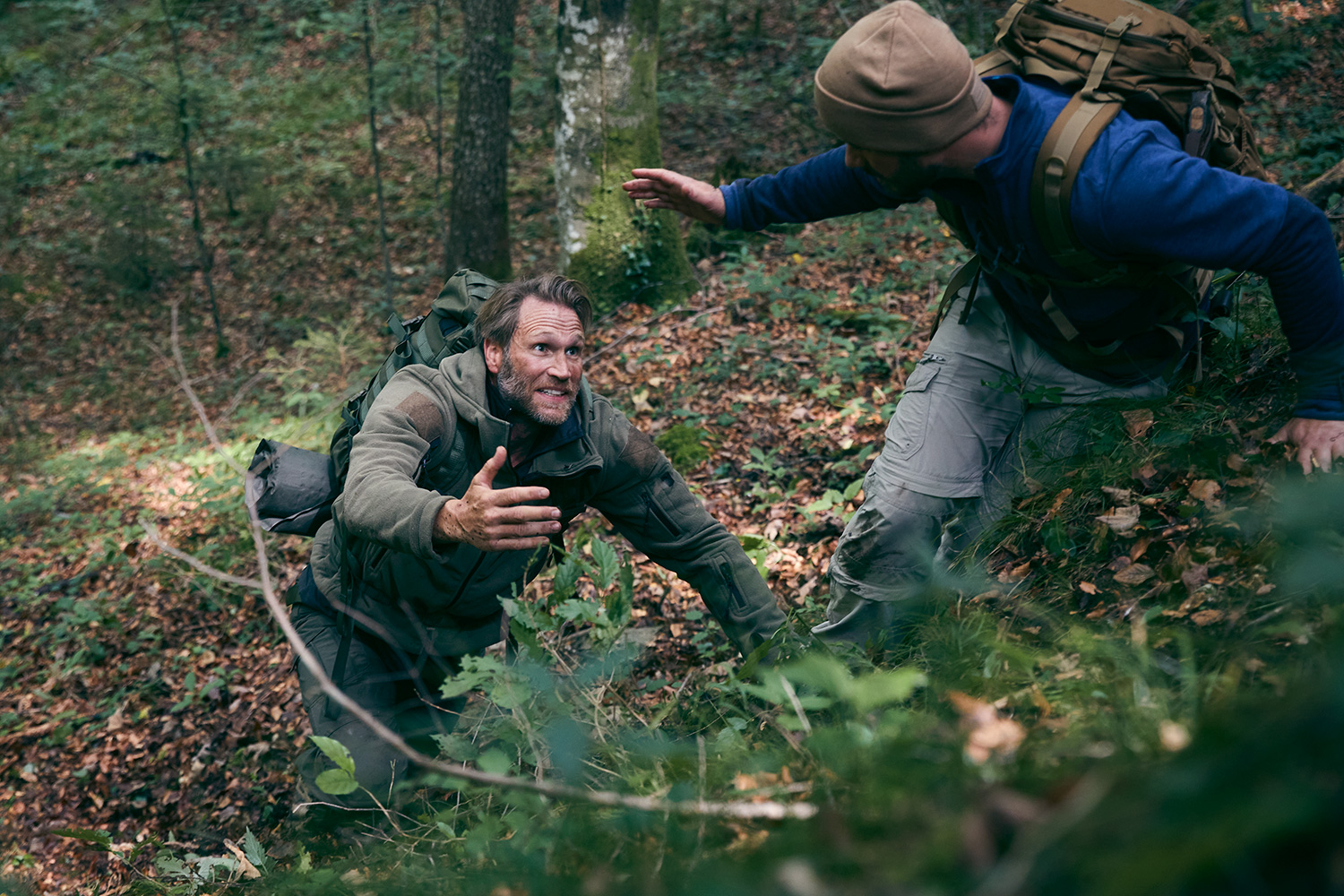 Survival trainer giving a man a hand while climbing up an embankment in the forest