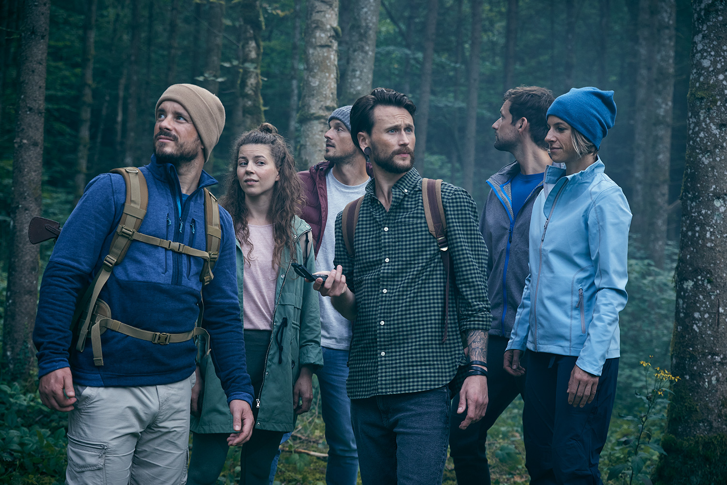 Five friends in the woods navigating with a compass