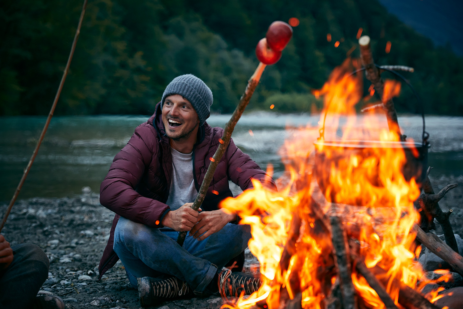 Man sitting around a campfire on the banks of a river, laughing and holding an apple on a stick