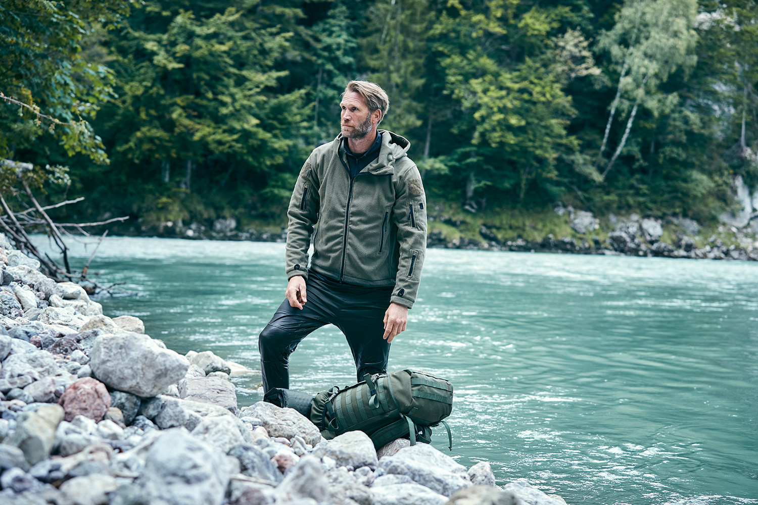 Man standing next to a fast river with his backpack next to him