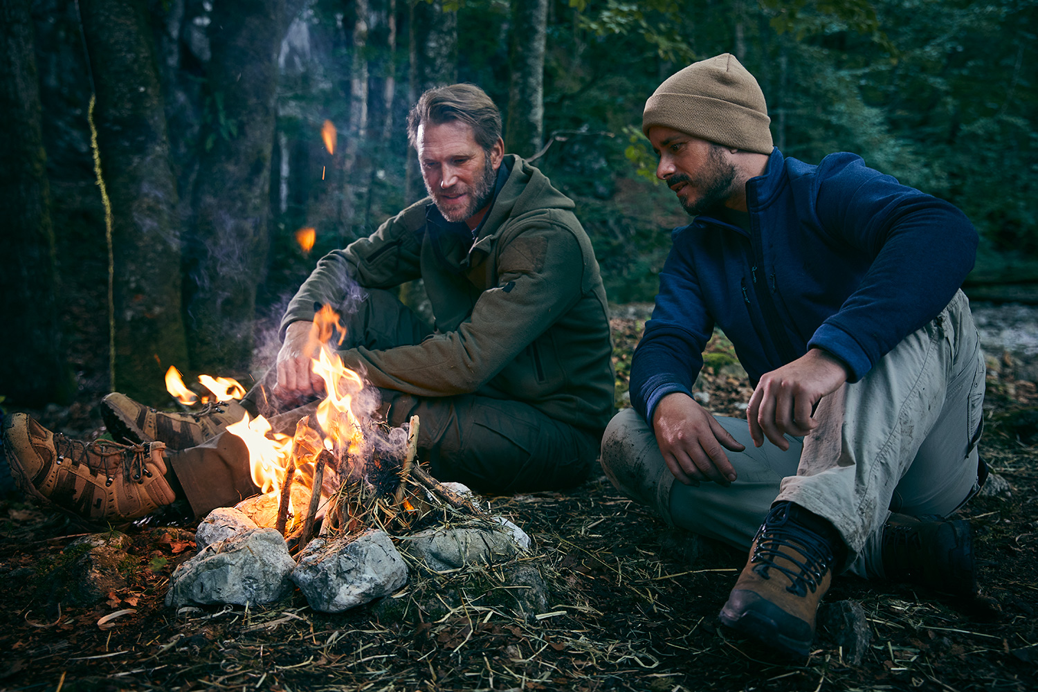 Survival trainer and his client sitting around a fire in the woods