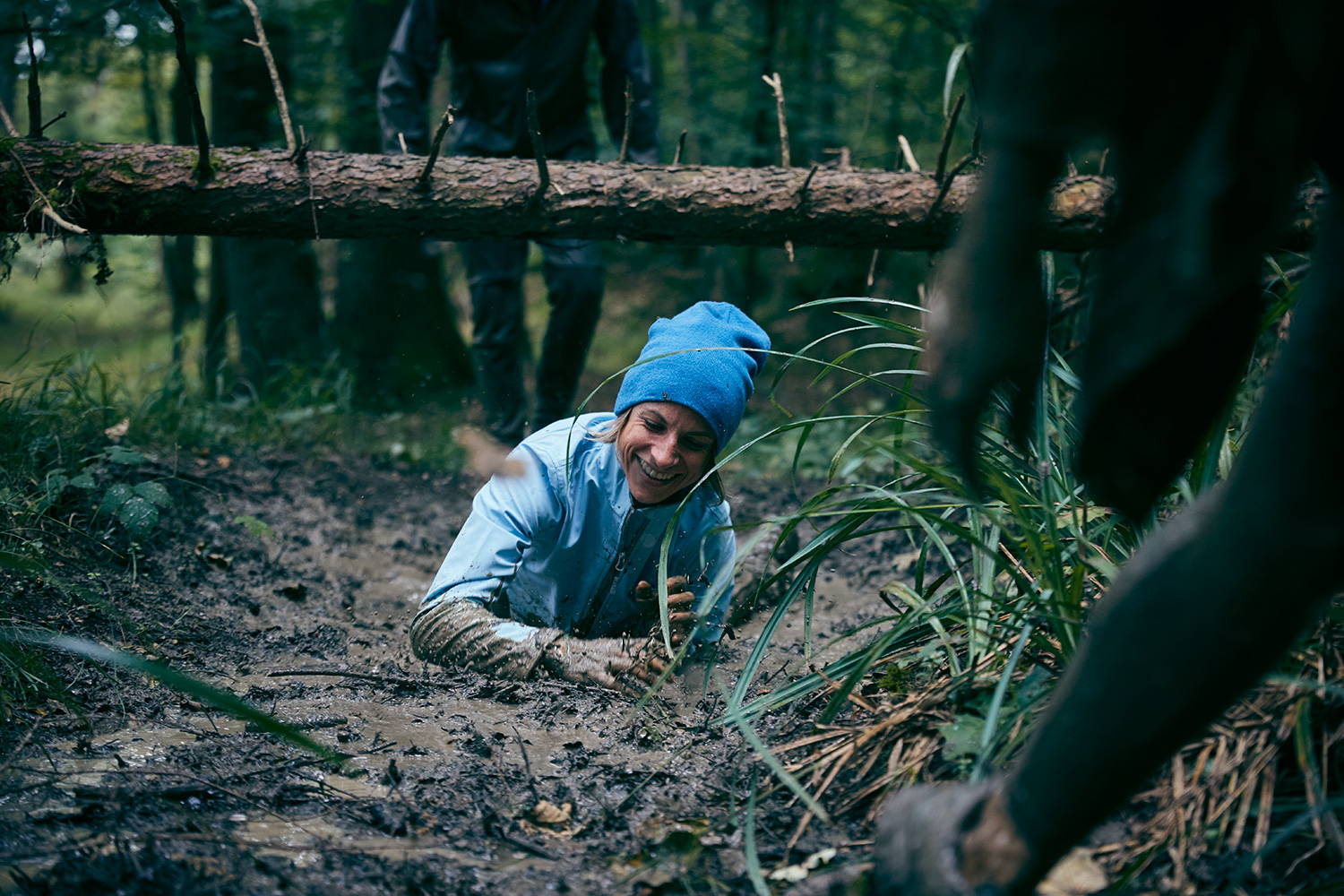 Woman robbing through a mud puddle on a Jochen Schweizer survival camp