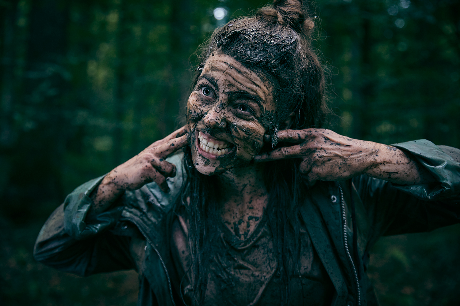 Woman making a scary face having bathed in mud