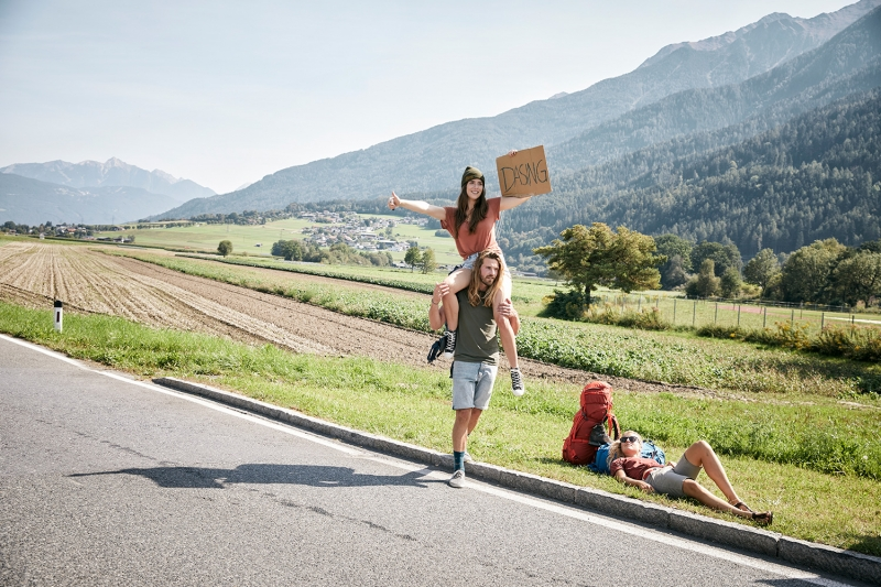 Three friends hitchhiking at the side of the road towards Dasing with their TATONKA backpacks