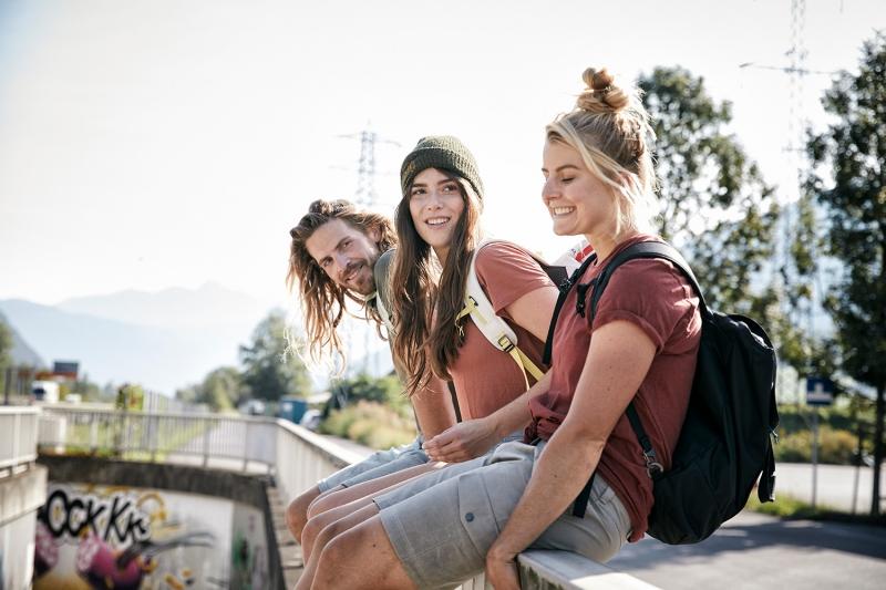 The friends sitting on the railing of an underground subway wearing TATONKA backpacks