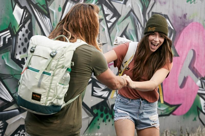 A boy and a girl having fun skateboarding infront of a graffiti wall for TATONKA Catalogue Shoot