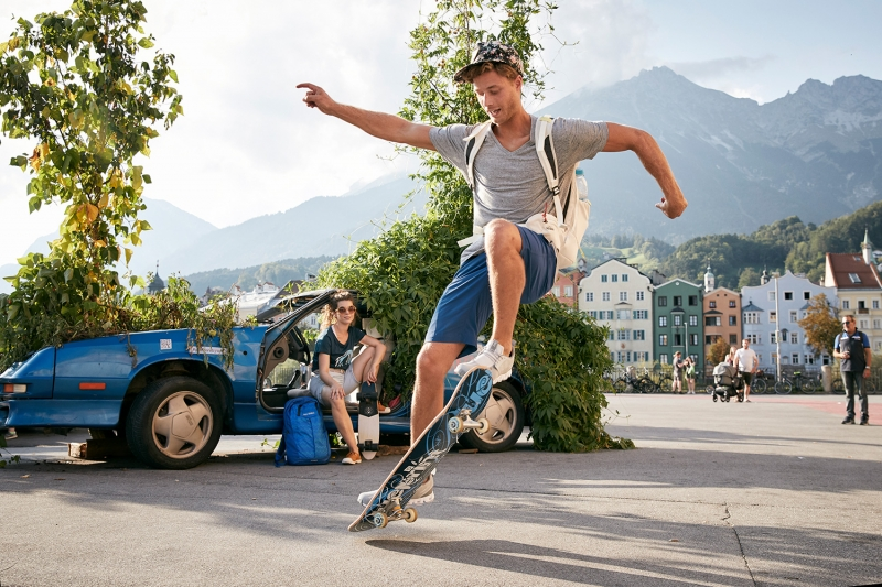 Boy doing skateboard tricks infront of his girlfriend in a plant car on the marketplace of Innsbruck