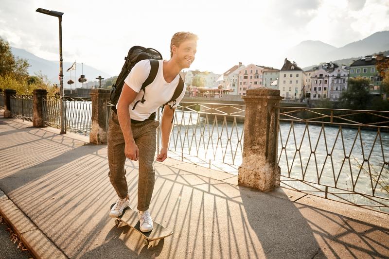 Boy skating along the Inn river across from Mariahilf while the sun sets behind him
