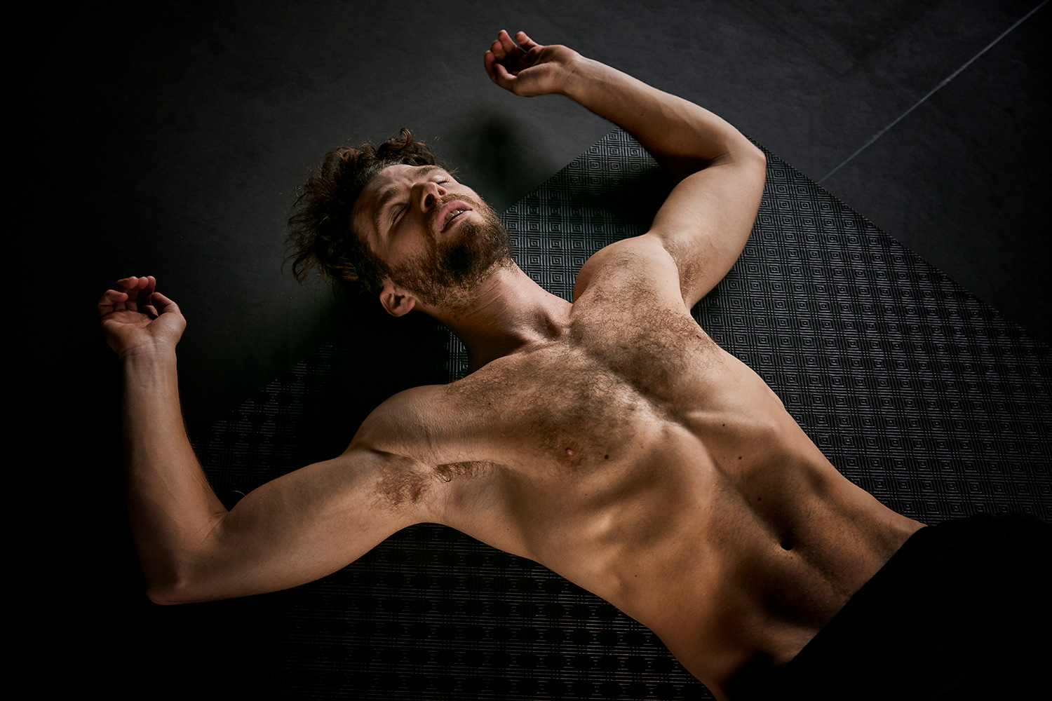 Exhausted man lying on the ground after a fitness session in a gym