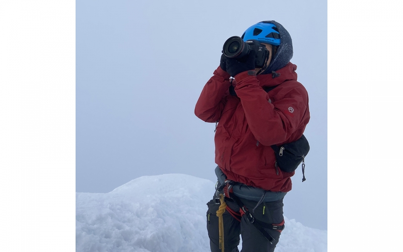 Jessica Zumpfe standing on the summit of the Grossglockner mountain on a photoshoot