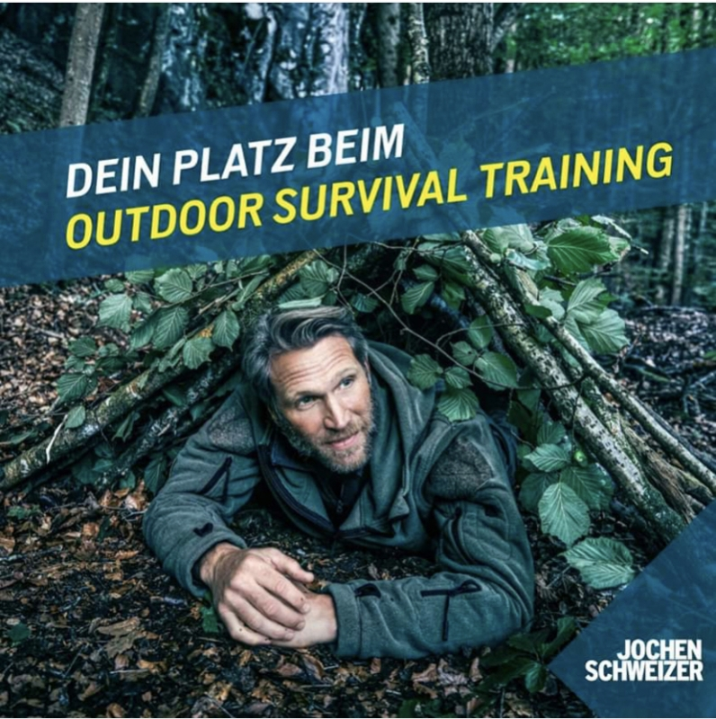 Advertisement for Jochen Schweizer Survival training of a man lying in his homemade shelter in the woods