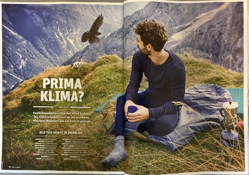 Double spead of a photo in Outdoor Magazin of a man sitting in thermals drinking coffee ontop of a mountain while a bird flies past