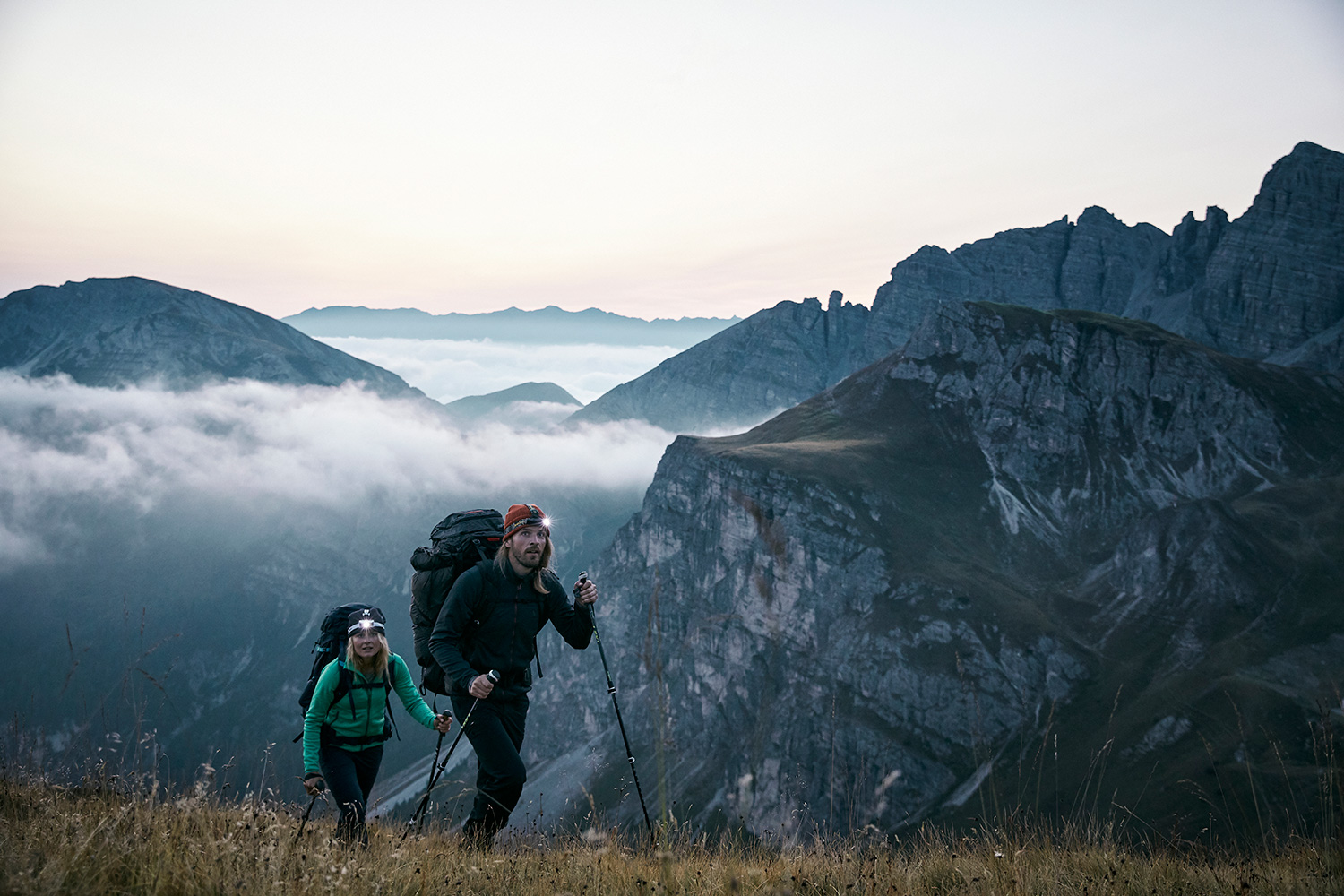 A couple hiking up to the summit before dawn, wearing their headlamps