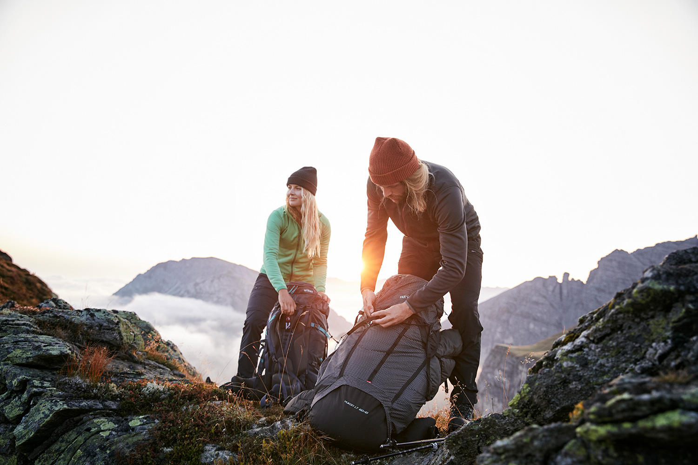 A couple taking off their TATONKA backpacks at sunrise ontop of Axamer Lizum in Austria