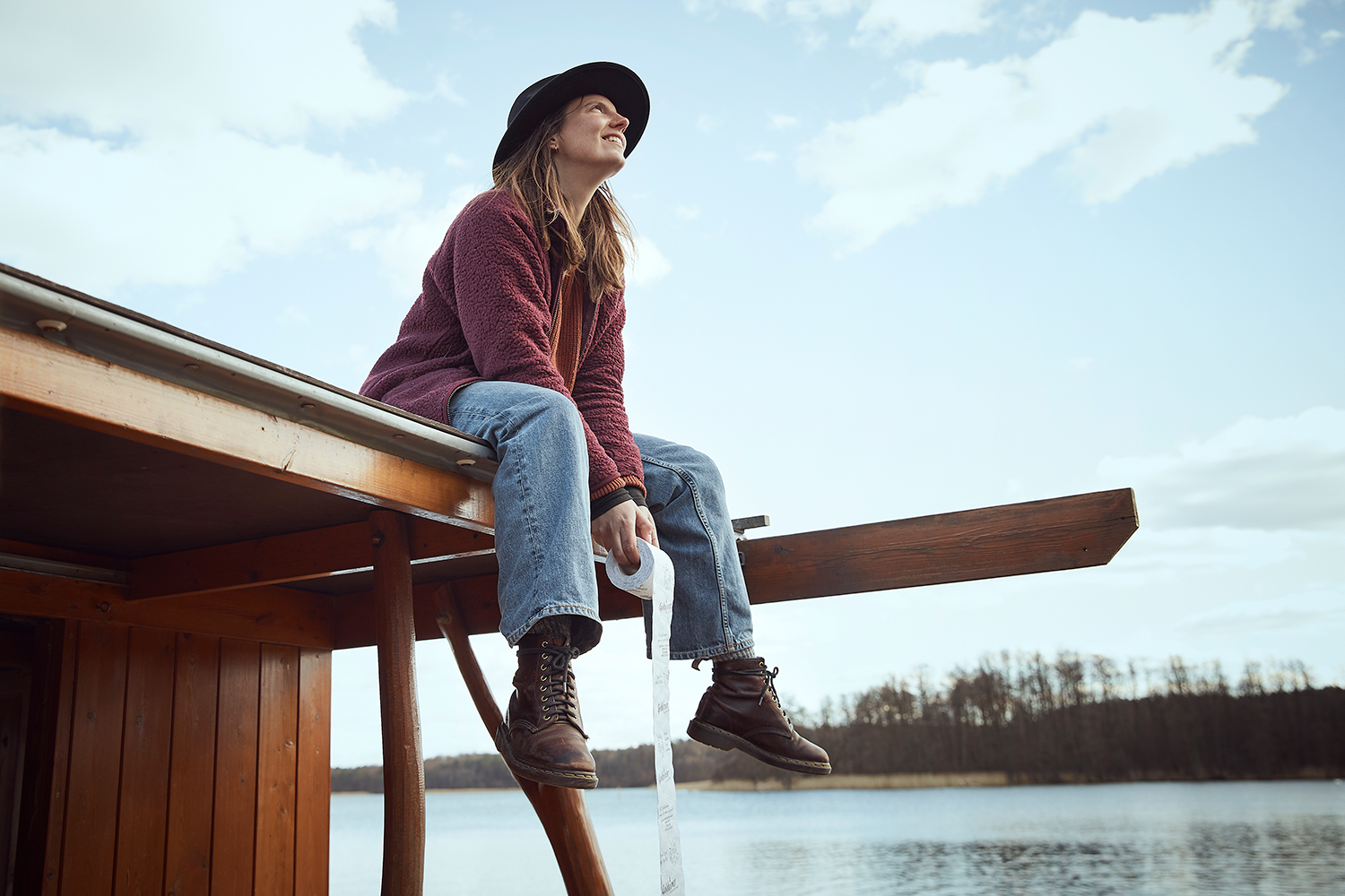 Girl sits on the roof of a raft holding a goldeimer toilet roll